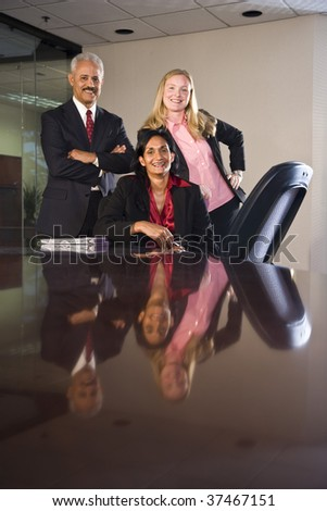 Multi-ethnic businesspeople in boardroom - stock photo