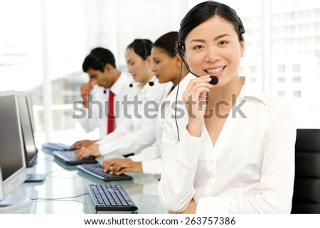Multi ethnic Call Center. Selective focus on Asian woman on foreground. - stock photo