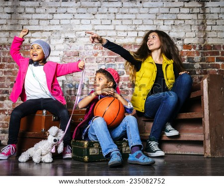 Multi-ethnic children group portrait in studio on brick-wall background - stock photo