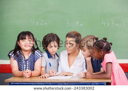 Multi ethnic classroom with teacher explaining mathematics lesson. - stock photo