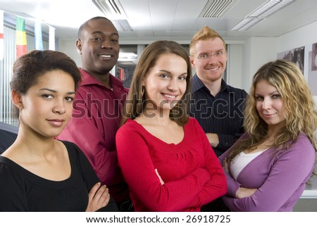 Multi-ethnic co-workers posing in office - stock photo