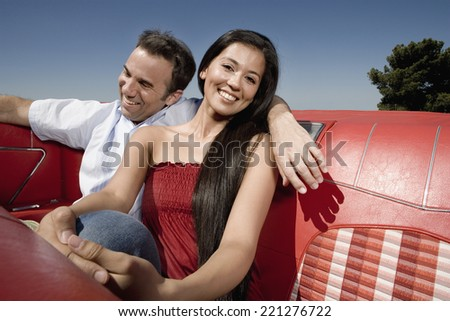 Multi-ethnic couple in backseat of convertible - stock photo