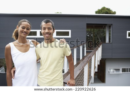 Multi-ethnic couple in front of house - stock photo