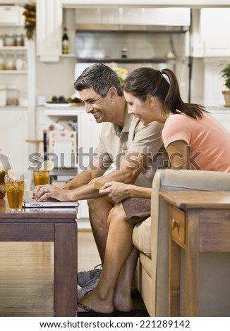 Multi-ethnic couple looking at laptop