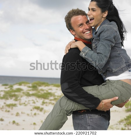 Multi-ethnic couple playing at beach