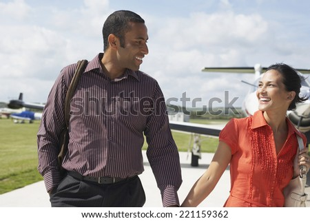 Multi-ethnic couple walking away from airplane - stock photo