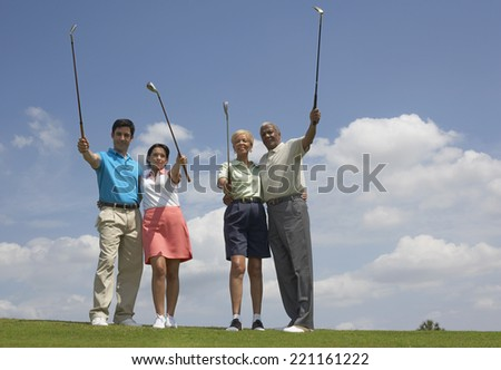 Multi-ethnic couples holding golf clubs - stock photo