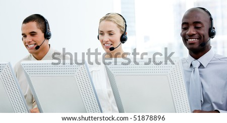 Multi-ethnic customer service representatives working in a call center - stock photo