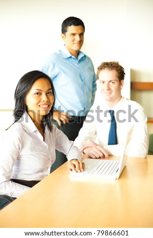 Multi-ethnic diverse group of attractive business people smile looking at camera during a conference room meeting using a laptop led by a beautiful Asian businesswoman. Vertical