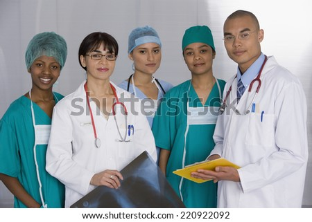 Multi-ethnic doctors discussing chart - stock photo
