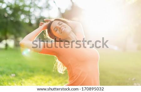 Multi-ethnic girl enjoying the warmth of a sunset - stock photo
