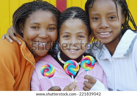 Multi-ethnic girls holding lollipops - stock photo