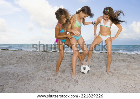 Multi-ethnic girls playing soccer at beach - stock photo