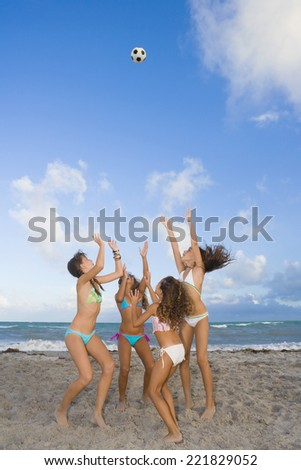 Multi-ethnic girls playing with soccer ball at beach - stock photo