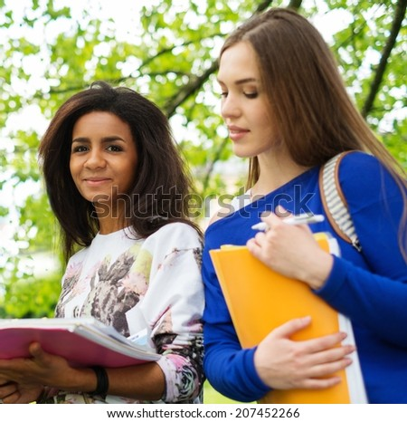 Multi ethnic girls students in a city park