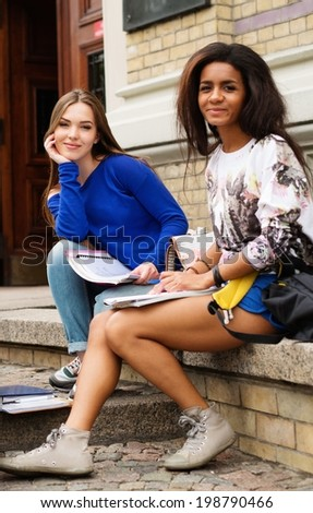 Multi ethnic girls students near university building entrance - stock photo
