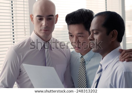 Multi-ethnic group of businessmen reading financial document - stock photo