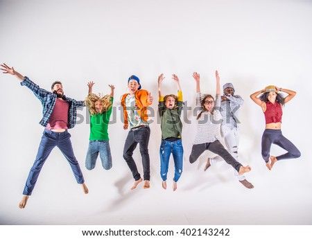 Multi-ethnic group of friends jumping on white background, studio shot - stock photo