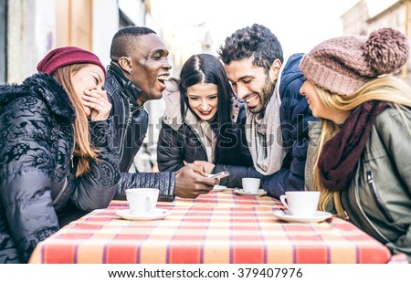 Multi-ethnic group of friends sitting in a bar and drinking coffee and watching a funny video on a cellular phone - Cheerful students meeting in a coffee house for a break - stock photo