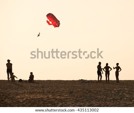 Multi-ethnic group of friends standing on the beach and talking - a group of young people silhouettes at sunset with paraglider flying on the background in sunset sky, Blurred background