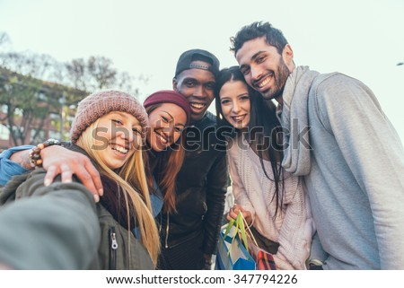 Multi-ethnic group of friends taking a selfie with cellphone outdoors - Young people photographing themselves - stock photo