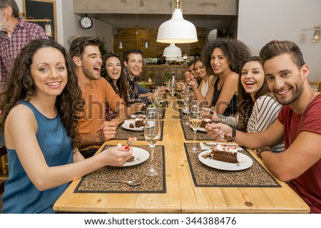 Multi-Ethnic Group of happy friends lunching and tasting the dessert at the restaurant - stock photo
