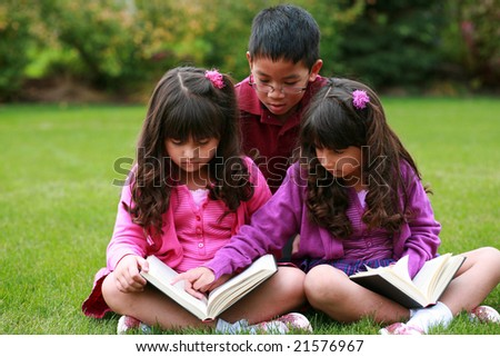 multi ethnic group of kids reading in grass - stock photo