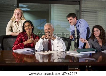 Multi-ethnic group of office workers in boardroom - stock photo