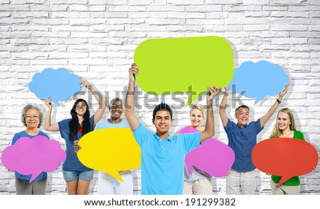 Multi-ethnic group of people holding colorful speech bubbles. - stock photo