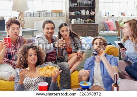 Multi ethnic group of  student friends bonding over sports match on TV drinking beer eating snacks  hanging out at home - stock photo
