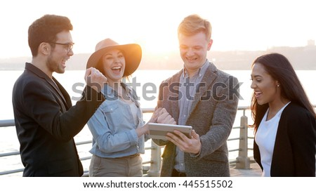 multi ethnic group of young friends having fun together. diverse team of business professionals looking at tablet computer screen talking chatting about new ideas   - stock photo