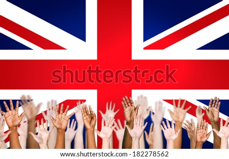Multi-Ethnic Hands Raised With British Flag In Background - stock photo