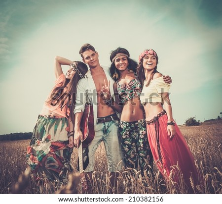 Multi-ethnic hippie friends with guitar in a wheat field  - stock photo