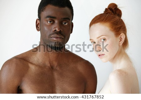 Multi-ethnic love and relationships concept: young redhead Caucasian woman wearing no clothes standing next to her naked African boyfriend, looking at the camera with serious expression on their faces - stock photo
