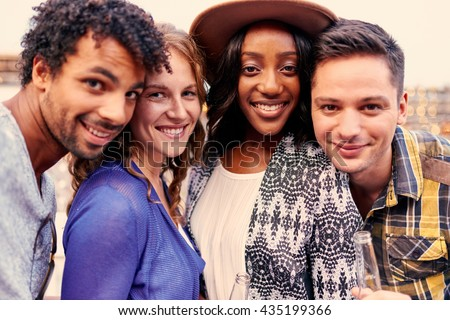 Multi-ethnic millenial group of friends taking a selfie photo with mobile phone on rooftop terrasse at sunset - stock photo