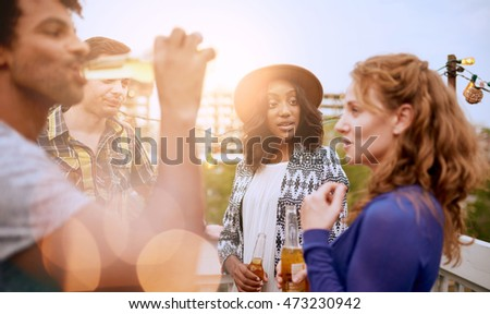 Multi-ethnic millennial group of friends partying and enjoying a beer on rooftop terrasse at sunset