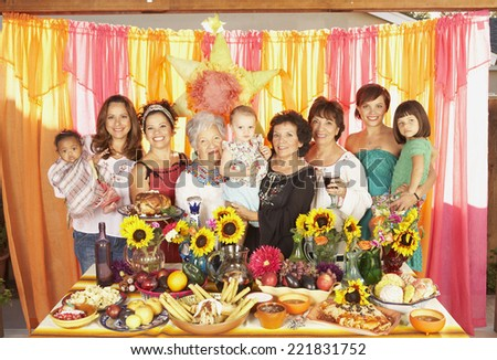 Multi-ethnic Mixed Race female family members behind buffet table - stock photo