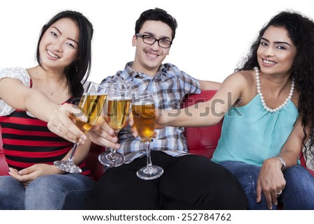 Multi-ethnic people smiling at the camera while toasting champagne, isolated on white