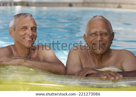 Multi-ethnic senior men in swimming pool - stock photo