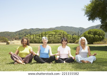 Multi-ethnic senior women meditating - stock photo