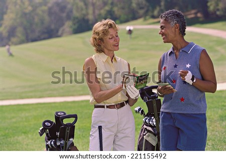 Multi-ethnic senior women on golf course - stock photo