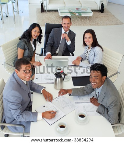 Multi-ethnic smiling business people working in a meeting - stock photo