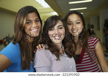 Multi-ethnic teenaged girls hugging in school hallway - stock photo