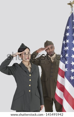 Multi-ethnic US military officers saluting American flag over gray background - stock photo
