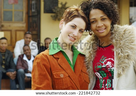 Multi-ethnic women hugging with friends in background - stock photo
