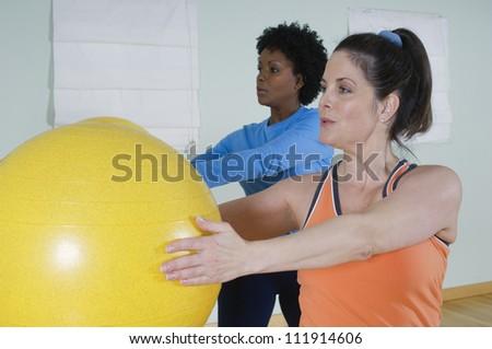 Multi ethnic women using exercise balls in fitness class - stock photo