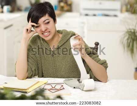 Multi-ethnic Young Woman Agonizing Over Financial Calculations in Her Kitchen. - stock photo
