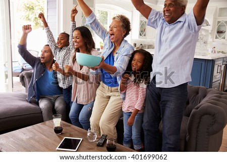 Multi generation black family watching sport on TV celebrate - stock photo