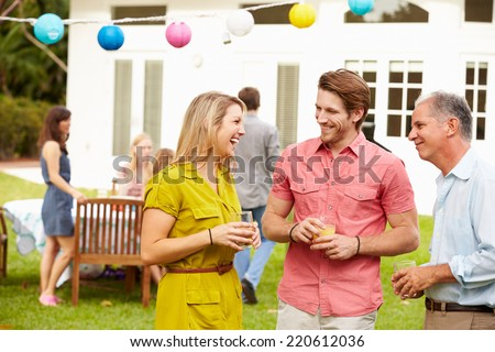 Multi Generation Family Enjoying Meal In Garden Together - stock photo