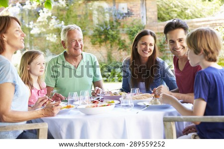 Multi Generation Family Enjoying Outdoor Meal Together - stock photo